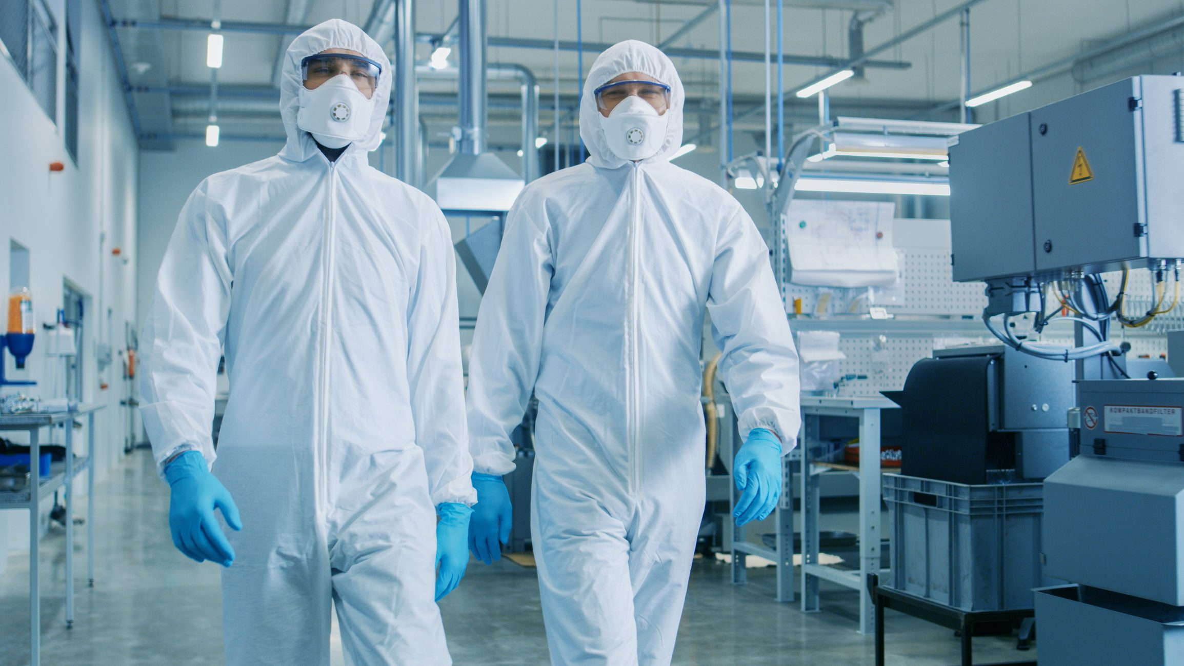 Cleanroom environment photo of two people walking through the room.
